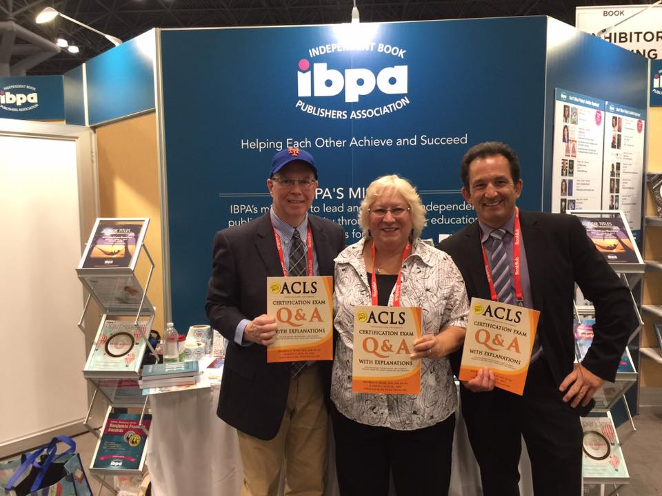 "Joe and Michele with their ""ACLS Q&A With Explanations"" certification exam prep book, on display at the IBPA booth, at the Book Expo at the Javitz Center, in NYC."